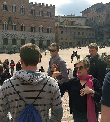 Prof. Jill Lamberton talks with students about Siena's famed public plaza, the Campo.