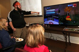 Tom Witkowski '15 walks kids  through a game he created at the inaugural Wabash Game Jam on April 27.