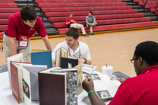 Current students pour over the Yearbooks of alumni back on campus