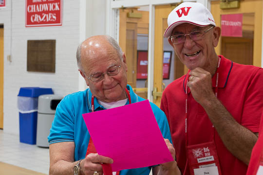 "Bob Witherspoon, song leader for the Class of 1965, and Don Schick check out the ""subdued"" cheat sheets for Old Wabash."